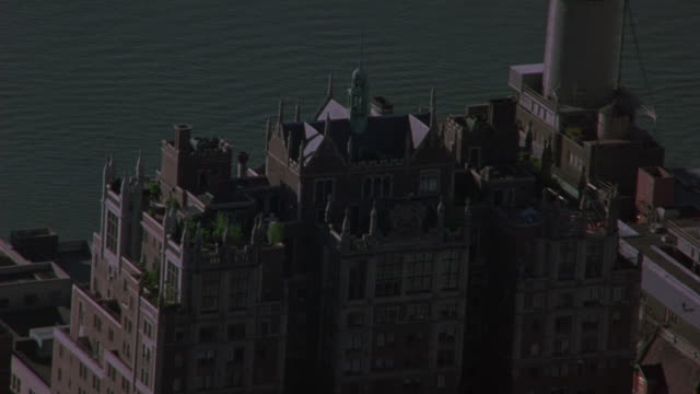 aerial of penthouse of brick apartment building with ramparts and spires. could be hotel. tudor city apartments, penthouse. upper class. con edison smoke stack, spire of chrysler building briefly visible.  midtown manhattan. east river. - tudor stock videos and b-roll footage