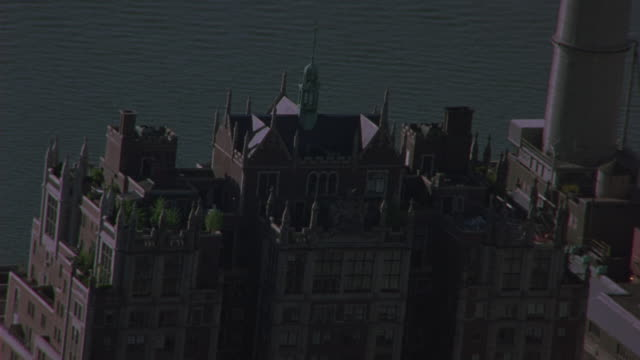 aerial of penthouse of brick apartment building with ramparts and spires. could be hotel. tudor city apartments, penthouse. upper class. con edison smoke stack, spire of chrysler building briefly visible.  midtown manhattan. east river visible. - spire stock videos & royalty-free footage
