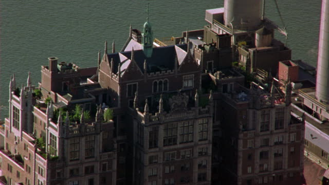aerial of penthouse of brick apartment building with ramparts and spires. could be hotel. tudor city apartments, penthouse. upper class. spire of chrysler building briefly visible.  midtown manhattan. east river visible. - penthouse stock videos and b-roll footage