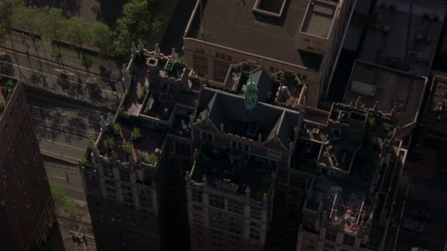 aerial birdseye pov over penthouse of brick apartment building with ramparts and spires. terraces, roof visible. tudor city apartments. upper class. midtown manhattan, east side. new york city skyline. - tudor stock videos and b-roll footage
