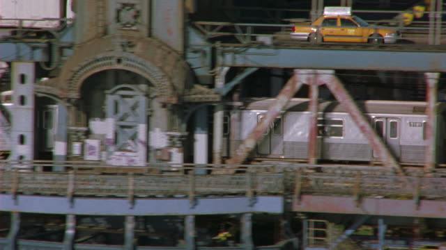 aerial of a subway car crossing the double decker manhattan bridge over the hudson river. shot pans up from bridge to new york city skyline with the brooklyn bridge in the fg and the twin towers in the bg. - anno 2001 video stock e b–roll