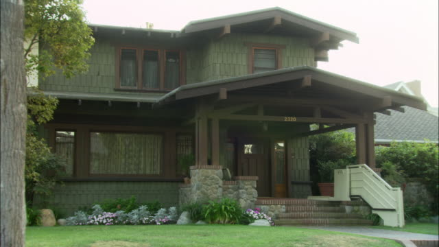 "pan left to right to show porch and front entrance to craftsman style bungalow. two story house has shingled walls, exposed wooden beams and stone foundation. address reads ""2320."" there is an electric handicap-access chair or ramp on the right side of po - electric chair stock videos & royalty-free footage"