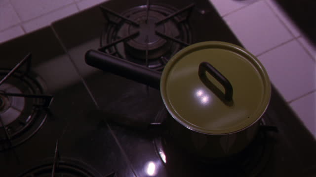 CLOSE ANGLE OF AN AVOCADO GREEN  1960S OR 1970S STYLE SAUCE PAN WITH LID SIMMERING ON TOP OF A GAS RANGE  STOVETOP. SEE WHITE TILE AROUND STOVETOP. KITCHENS. COOKING. APPLIANCES.