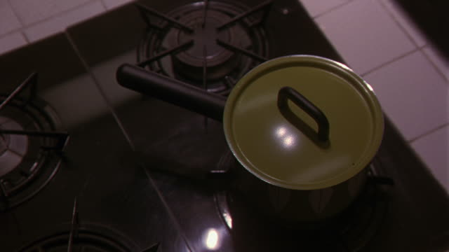 CLOSE ANGLE OF AN AVOCADO GREEN, LATE 1960S OR 1970S STYLE POT WITH LID SIMMERING ON A GAS RANGE STOVETOP. SEE WHITE TILED COUNTER NEXT TO STOVE. COOKING. APPLIANCES. KITCHENS.