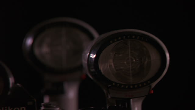 CLOSE ANGLE OF A 1970S NIKON CAMERA WITH THREE HONEYWELL STROBONAR FLASH BULBS ATTACHED. CAMERA PANS LEFT TO RIGHT  BRINGING DIFFERENT FLASHBULBS INTO FOCUS. A BRIGHT LIGHT FLASHES THREE TIMES FROM OFF FRAME IN DARKENED ROOM. COULD ALSO BE EXTERIOR AT NIG