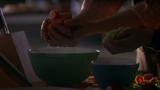 close angle of a kitchen table top with pyrex primary color mixing bowls, chopped carrots and a drinking glass. a child's hands holding chopped celery and a woman's hands with chopped carrots enter the frame and  throw the vegetables into the bowls. see a - color block stock videos and b-roll footage