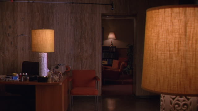 wide angle shows a 1970s style office waiting room.  study or psychologist's office visible through door in background. waiting room contains an orange chair, retro lamps, and a desk with electric typewriter and office supplies. the inner office has a boo - electric chair stock videos & royalty-free footage