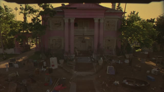 vidéos et rushes de high angle down of shabby pink greek revival two story mansion with shady front yard covered in garage sale items. yard has dead grass.  junk includes a refrigerator, appliances, furniture, and clothing. house has ionic columns, balcony, and cluttered por - vide grenier