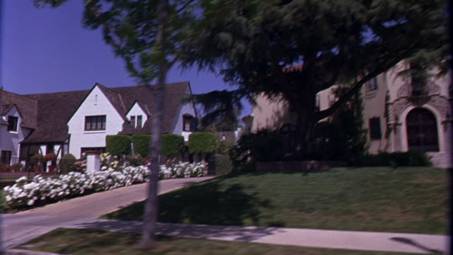 PROCESS PLATE STRAIGHT RIGHT SIDE SHOWS STREET SIGN 'HUDSON PL 100 S'  AS POV BEGINS DRIVING THROUGH AN UPPER MIDDLE CLASS LOS ANGELES NEIGHBORHOOD, HANCOCK PARK. SEE GREEN LAWNS AND MANICURED FRONT YARDS, PALM TREES AND LAMP POSTS LINING STREETS, SIDEWAL