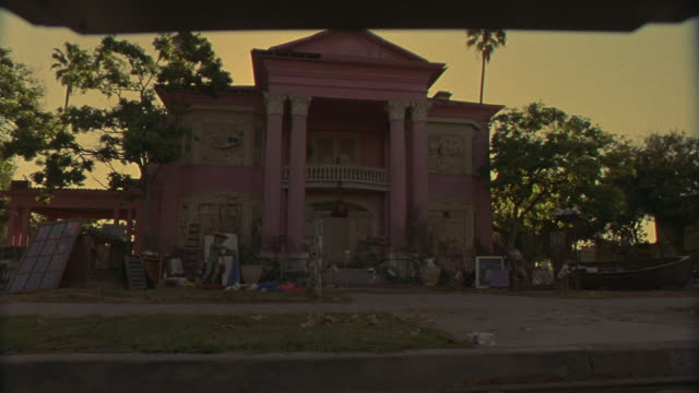 vidéos et rushes de up angle of shabby pink greek revival two story mansion with shady front yard covered in garage sale items. camera pans slowly right then left to show yard with dead grass and junk including a refrigerator, dinghy, statue, bookshelves, windows, furniture, - vide grenier