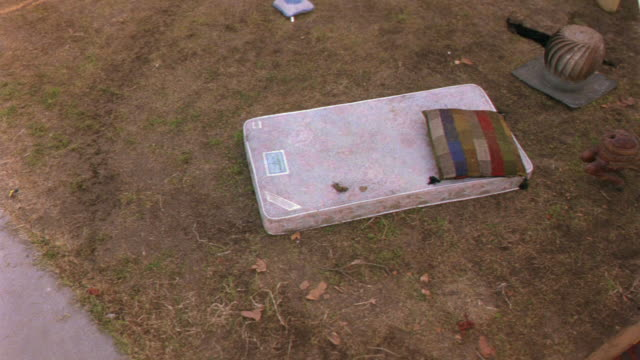 vidéos et rushes de aerial of lawn covered in bizarre yard sale items. the macabre garage sale has an assortment of clutter including a dirty mattress, bird cage, pillows, a sink, a statue, broken furniture, carpets, kewpie dolls, a wooden dinghy full of plates, and mugs. se - vide grenier
