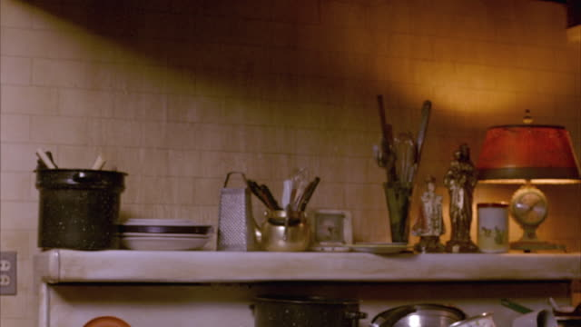 vídeos y material grabado en eventos de stock de medium angle shows a cluttered kitchen shelf on top of a stove with colander, plates, cheese grater, jesus christ figurine, lamp with clock in base and utensils. pots and pans also visible. - estante muebles