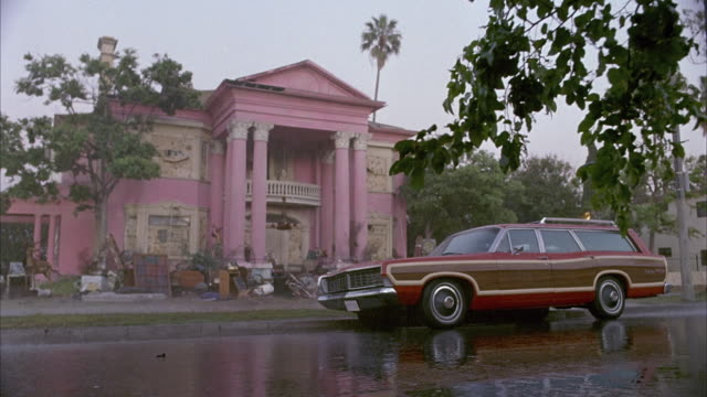 vidéos et rushes de wide angle from low pov shows a shabby pink greek revival two story mansion in the rain. an early 1968 ford ltd country squire station wagon with fake wood paneling and a luggage rack is parked in front. the front yard is filled with clutter as if occupan - vide grenier