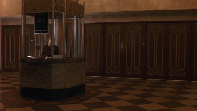 MEDIUM ANGLE SHOWS ENTRY WAY OF THE ART DECO STYLE WARNER GRAND THEATER. WOMAN IN USHER'S UNIFORM IS VISIBLE IN TICKET OFFICE AS PATRONS EXIT THEATER THROUGH ORNATELY DECORATED DOORS. PEOPLE WEAR HEAVY COATS, LATE 1970S STYLE CLOTHING. MOVIE THEATER.