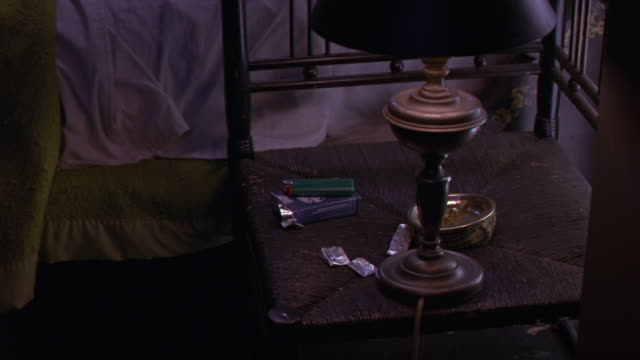 MEDIUM ANGLE OF BRASS LAMP, ABALONE SHELL ASHTRAY, PACK OF CIGARETTES, LIGHTER AND STICKS OF GUM ON A BEAT UP CHAIR SERVING AS A NIGHT STAND. THERE IS AN UNMADE BED IN THE BACKGROUND WITH AVOCADO GREEN BLANKETS. COULD BE USED FOR BEDROOM IN A LOW RENT MOT