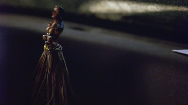 close angle of a dashboard figurine, hula dancer doll wiggling in a darkened car interior. doll appears to be a hawaiian woman with long skirt. dancing. decorations. - doll stock videos & royalty-free footage