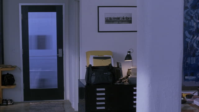 MEDIUM ANGLE OF HOME OFFICE. SEE BLACK METAL FILE CABINET WITH DESK LAMP AND DUFFEL BAG ON TOP. SEE DOOR WITH FROSTED GLASS WINDOW PANE. SEE LUNCH ATOP A SKYSCRAPER FRAMED PRINT ON WALL.