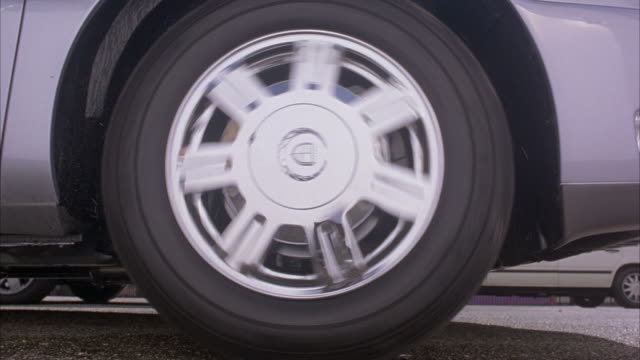 vídeos de stock, filmes e b-roll de close angle of chrome seven spoke cadillac wheel or rim. see wheel spin as grey cadillac sts speeds away. could be burnout. see cadillac move away to reveal medium angle of saturn and volvo parked in front of white apartment building. - cadillac