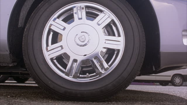 vídeos de stock, filmes e b-roll de close angle of chrome seven spoke cadillac wheel or tire or rim. see wheel spin as grey cadillac sts speeds away. could be peeling out. see cadillac move away to reveal medium angle of saturn and volvo parked in front of white apartment building. - cadillac