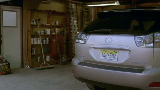 medium angle of silver lexus rx330 parked in garage with door open. see shelves with paint cans on top. see brooms. see new jersey license plate on car. - rx stock videos & royalty-free footage