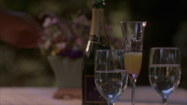 close angle of bottle of champagne sitting next to two glasses of water and one glass of mimosa. see flower arrangement centerpiece blurred in background. see woman's hand reach in and pour more champagne into half filled glass of mimosa, pick it up, and - french manicure stock videos and b-roll footage