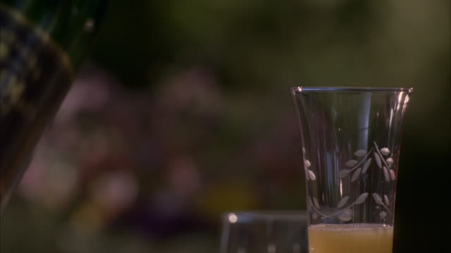 close angle of half filled etched glass of mimosa sitting on table.  see flower arrangement centerpiece and bottle of champagne blurred in background. see woman's hand reach in and pour more champagne into half filled glass of mimosa, pick it up, and exit - french manicure stock videos and b-roll footage