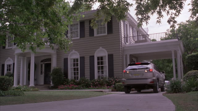 medium angle of silver lexus rx330 reversing out of driveway. two-story upper class house with gray and blue trim. - zweistöckiges wohnhaus stock-videos und b-roll-filmmaterial