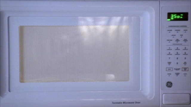 CLOSE ANGLE OF BAG OF POPCORN POPPING IN MICROWAVE.