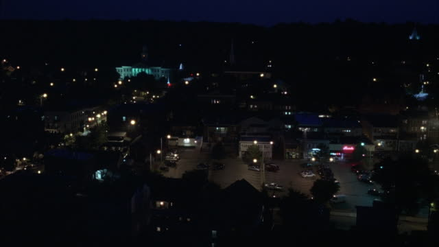 ESTABLISHED WIDE ANGLE OF SMALL TOWN ON HILLSIDE WITH DENSE TREES IN BACKGROUND. VERY DARK SHOT. SMALL LOW STORY BUILDINGS, NEW ENGLAND STYLE. LIT WHITE GOVERNMENT BUILDING OR CITY HALL IN LEFT BACKGROUND. STREET LAMPS LIT AROUND TOWN. SEE TRAFFIC MOVING