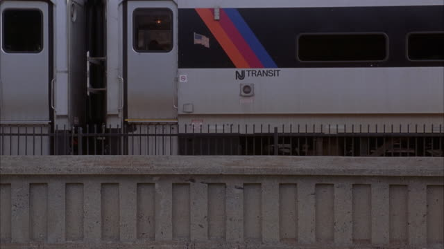 """medium angle of train station platform. metal fence and concrete fence in foreground, could be divider. """"cranford"""" sign on left. see interior of station with benches and trash can behind metal fence. train appears from right and stalls behind metal fence. - new jersey stock videos & royalty-free footage"""