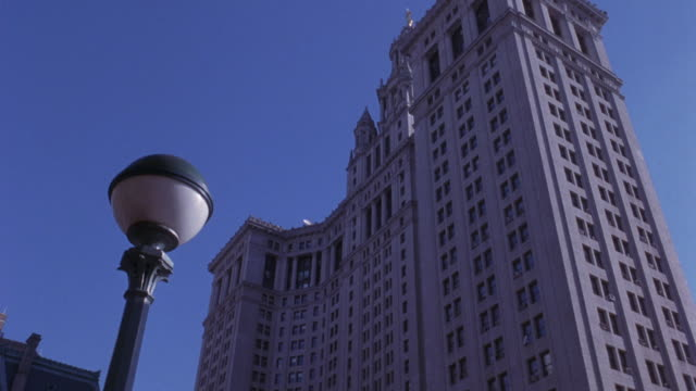 stockvideo's en b-roll-footage met pan up to new york city hall multi-story office building downtown. see lamp post in foreground. government building manhattan. - town hall