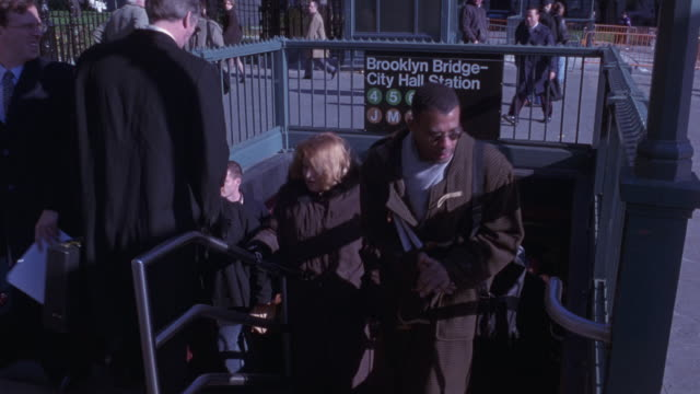 "MEDIUM HIGH ANGLE DOWN OF SUBWAY STATION STEPS. SEE COMMUTERS WALKING UP AND DOWN STEPS. COULD BE BUSINESSMEN WEARING SUITS, BUSINESS WOMEN, BUSINESS PEOPLE. SEE SIGN ABOVE STEPS READING ""BROOKLYN BRIDGE - CITY HALL STATION."""
