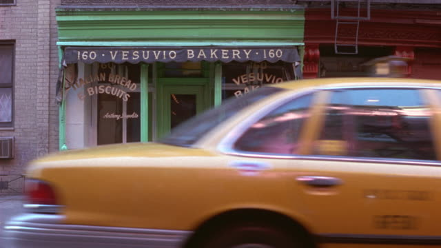 "medium angle of green painted storefront or store. see awning above entrance with sign reading ""vesuvio bakery"". see shop windows with painted writing ""italian bread & biscuits"" and ""vesuvio bakery"". see loaves of bread sitting in window and bags of bread - bakery stock videos & royalty-free footage"