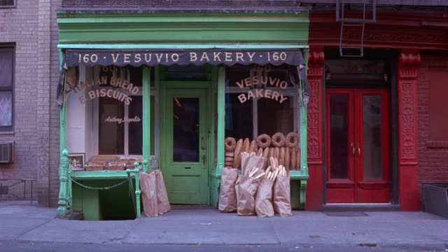 "medium angle of green painted storefront or store. see awning above entrance with sign reading ""vesuvio bakery"". see shop windows with painted writing ""italian bread & biscuits"" and ""vesuvio bakery"". see loaves of bread sitting in window and bags of bread - building storey stock videos and b-roll footage"