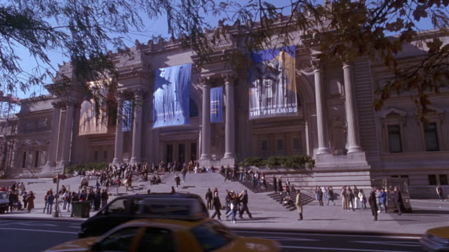 """vídeos y material grabado en eventos de stock de wide angle of metropolitan museum of art or met. see cars and taxis driving right to left on street, people or pedestrians walking up steps and on sidewalk. see banners hanging from museum facade and columns. one banner reads """"the pyramids"""". see tree bran - met"""