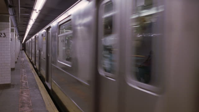"pan left to right of new york subway station. shot starts with close angle of silver subway car filled with commuters pulling away from station platform. pan left to follow train as it exits to tunnel on right. see subway car sign reading ""6"", manhattan - - underground rail stock videos & royalty-free footage"