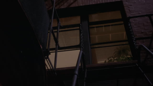 zoom in from outside of apartment building to window on looking living room. see fire escape at beginning. - fire escape stock videos and b-roll footage