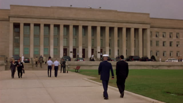 MEDIUM ANGLE OF PENTAGON WITH MILITARY OFFICERS CLIMBING STAIRS TOWARDS BUILDING. SEE PASSING TRAFFIC IN BACKGROUND. COULD BE GOVERNMENT BUILDING OR CITY HALL.