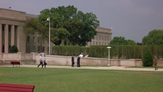 MEDIUM ANGLE OF PENTAGON WITH MILITARY OFFICERS CLIMBING STAIRS TOWARDS BUILDING. SEE TREE OBSCURING VIEW. COULD BE GOVERNMENT BUILDING OR CITY HALL.
