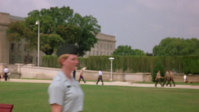 MEDIUM ANGLE OF PENTAGON WITH MILITARY OFFICERS CLIMBING STAIRS TOWARDS BUILDING. SEE TREE OBSCURING VIEW. FEMALE OFFICER WALKS PAST FOREGROUND. COULD BE GOVERNMENT BUILDING OR CITY HALL.