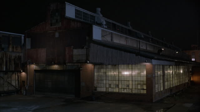medium angle of old rundown warehouse in industrial area. see lights dimly lit inside warehouse. - deposito video stock e b–roll