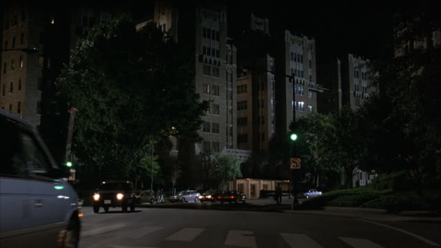 wide angle of multiple high rise apartment buildings at night. see cars driving on street. middle class neighborhood. - middle class stock videos & royalty-free footage
