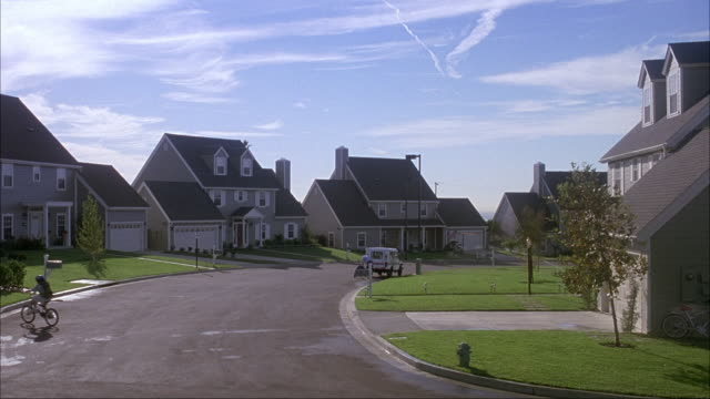 wide angle of suburban neighborhood. see multi-story houses on either side of street. see grass lawns in front of houses. see sprinklers watering lawn. see girl on bicycle riding screen right to left. see mailman and truck in distance. see white suv drive - driveway stock videos & royalty-free footage