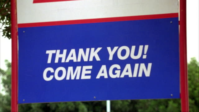 "medium angle of sign in parking lot. see red white and blue colors on sign. see text read ""thank you! come again."" see trees in background. - thank you stock videos and b-roll footage"