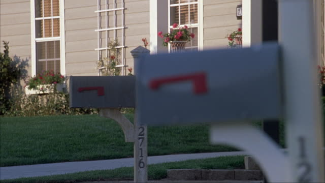 medium angle of two gray mailboxes planted in the front yards of suburban houses. see red flag on side of mailboxes down. see flowers growing along sides of houses with verdant lawns. - letterbox stock videos & royalty-free footage