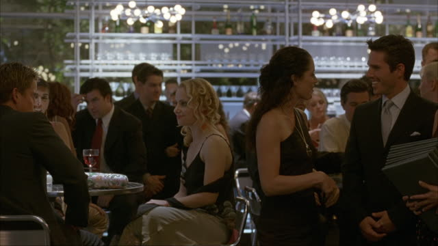 medium angle of men and women dressed in formal evening wear in restaurant. see chandeliers hanging in the background. waitress in black dress holds stack of menus as she chats with group of people. see camera pan left as they walk of the scene. see peopl - black dress stock videos & royalty-free footage