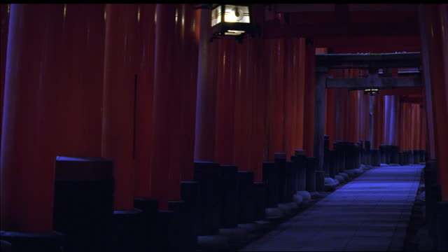 vidéos et rushes de wide angle of path or walk way covered by series of red wooden gates. could be japanese shinto shrine. lanterns hang from gates and stone path is lined with wood posts of varying heights. - sanctuaire