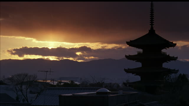 wide angle of japanese town at sunset. multi-story pagoda or temple or shrine sits in middle of town city, surrounded by houses or other buildings with tile roofs. rooftops. dark clouds in sky pass over sun on horizon. mountains in background. - pagoda点の映像素材/bロール