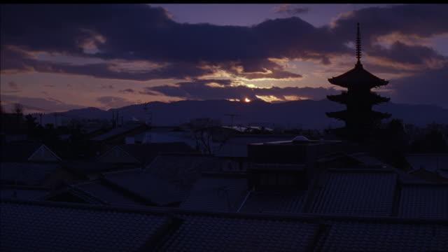 wide angle of japanese town at sunset. multi-story pagoda or temple or shrine sits in middle of town or city, surrounded by houses or other buildings with tile roofs. rooftops. dark clouds in sky pass over sun on horizon. sun rays, mountains in background - pagoda点の映像素材/bロール