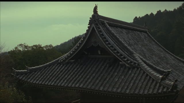 medium angle of tile roof of japanese pagoda, temple, or shrine. japanese architecture. mountains, trees, woods, forest in background. - shrine stock videos and b-roll footage